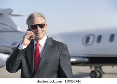 Confident senior businessman using cell phone with private jet in background