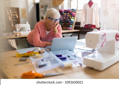 Confident senior fashion designer in her workshop
