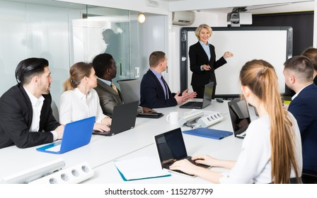 Confident senior female discussing business project with members of her team in boardroom