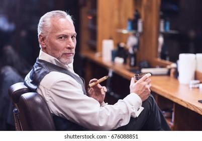 Confident senior man smoking a cigar