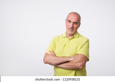 Confident senior man in yellow t-shirt crossing hands on chest and looking at camera while standing against gray background. Self confident hispanic senior.