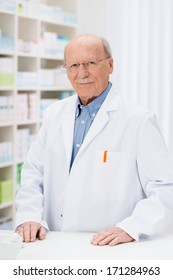 Confident senior pharmacist in his pharmacy standing behind the counter in front of stocked shelving smiling at the camera