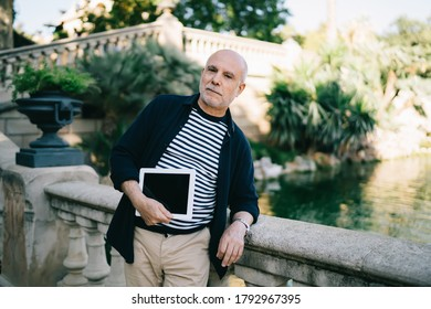 Confident senior unshaven man in casual wear standing near pond and leaning on stone banister while holding tablet in urban park