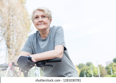 Confident senior woman leaning on bicycle's handlebar in park