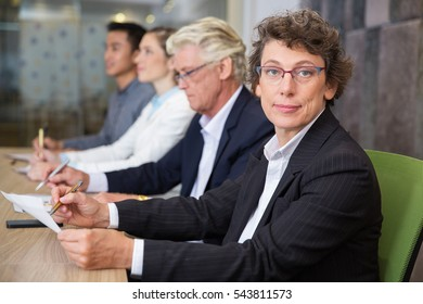 Confident senior woman sitting at conference