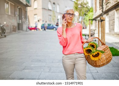 Confident senior woman uses smart phone while walking. Senior woman enjoys living in the city. Beautiful senior woman talking on mobile phone outdoors