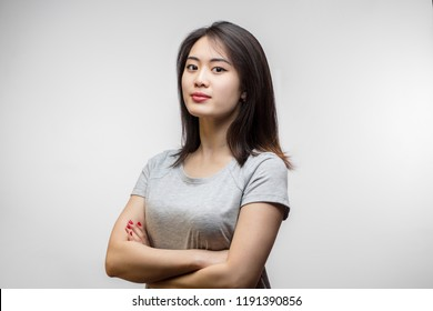 Confident sensual young Korean woman with long hair, dressed in white t-shirt looking at camera over white background. Youth and Beauty concept