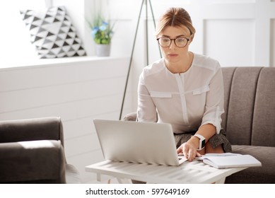 Confident serious business woman working on the laptop