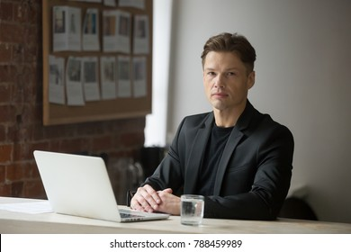 Confident serious businessman in suit sitting at workplace with laptop looking at camera, successful professional posing at office desk and computer, strict unsmiling company ceo boss portrait