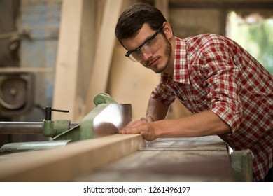 Confident and serious joiner grinding timber with help of special equipment. Busy carpenter in checked shirt and safety glasses working in joiner's shop. Handsome man working with wood.