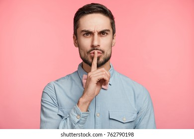 Confident serious male dressed formally, keeps index finger on lips, asks best friend to be quiet and not tell his secret to other people, isolated over pink background. Man gestures in studio