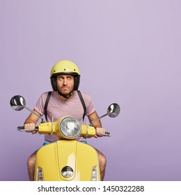 Confident serious man rides on motorcycle, focused aside, stops on way to have rest, wears helmet, casual purple t shirt, covers distance, travels alone, enjoys speed. Professional male rider on bike