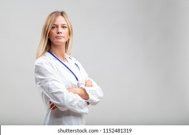 Confident serious young woman doctor wearing a lab coat and stethoscope standing with folded arms staring at the camera over white with copy space