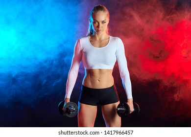 confident sexy woman in sporty clothes pumping up muscles with dumbbells isolated on black background.the beauty of body. lifestyle, hobby