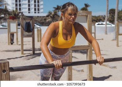 Confident shaped woman in sportswear doing exercise with bar on sandy gym outside on coastline looking forward.