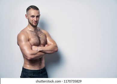 Confident shirtless muscular man standing with folded hands looking at camera