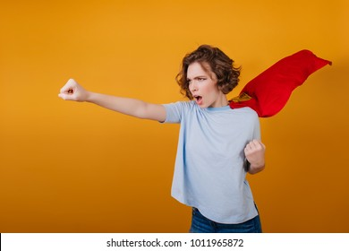 Confident short-haired girl posing in red superhero cloak. Studio shot of brave young woman in superwoman costume.