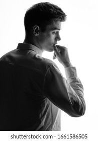 Confident silhouette portrait of young man in white shirt. Business or office worker concept. Isolated white background.