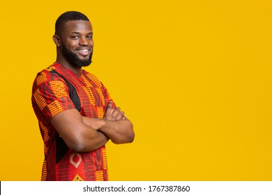 Confident smiling african american guy in bright traditional t-shirt over yellow studio background, copy space - Shutterstock ID 1767387860