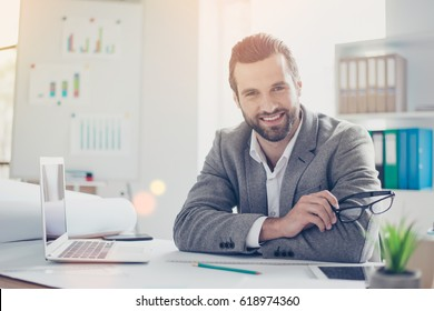 Confident smiling architect in formal wear  holds glasses and sitting at the table in office