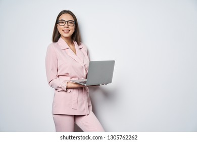 Confident smiling business woman wearing pink suit standing by white wall holding opened laptop looking at camera