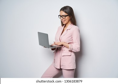 Confident smiling business woman wearing pink suit standing by white wall holding opened laptop surfing