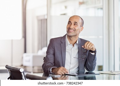 Confident smiling businessman looking at the side in modern office. Portrait of a pensive businessman looking up. Mature thinking businessman sitting at desk.