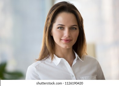 Confident smiling businesswoman looking at camera, successful entrepreneur, young professional manager or female business owner posing in office, beautiful millennial woman employee headshot portrait