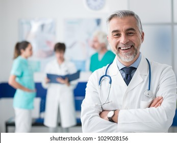 Zuverständiger lächelender Arzt posieren und das Krankenhaus mit gekreuzten Armen und medizinisches Team arbeitet auf dem Hintergrund