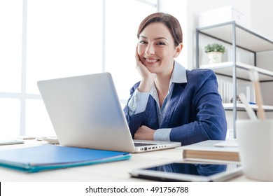 Confident smiling female executive posing in her office with hand on chin