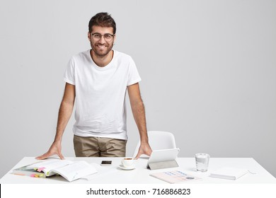 Confident smiling man does paper work, studies invoice, has coffee, works with modern technologies, stands at table in modern office, isolated over grey background. Male student prepares for exam
