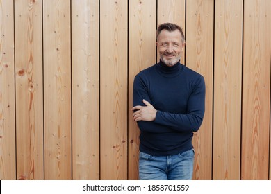 Confident smiling man in jeans and sweater with folded arms leaning nonchalantly against a wooden wall outdoors with copyspace