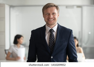 Confident smiling middle aged business man ceo banker coach in suit looking at camera, male company director owner professional manager posing in office, happy team leader employer head shot portrait