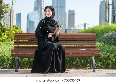 Confident and Smiling muslim arab woman in abaya holding tablet and looking in the camera.