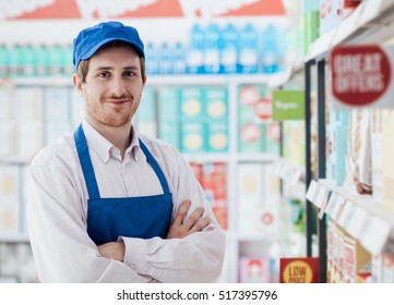 Confident smiling supermarket clerk posing at the shopping mall, retail job concept
