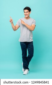 Confident smiling young Asian man pointing hands to empty space aside studio shot isolated on light blue bakground