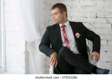 Confident smiling young businessman sitting on a white chair