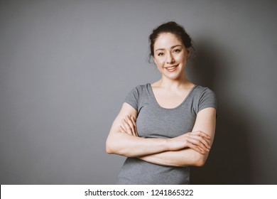 confident smiling young woman in her 20s with her arms folded against gray background with copy space