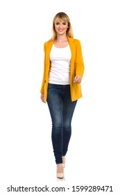 Confident smiling young woman in yellow unbuttoned jacket, blue jeans and high heels is walking towards camera. Front view. Full length studio shot isolated on white.