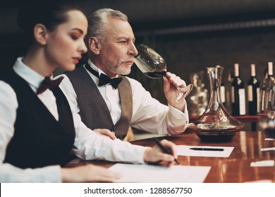 Confident sommelier tasting wine in restaurant. Checking taste, color, sediments of wine. Confident sommelier checks aging of wine
