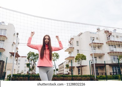 confident sports girl posing outdoors by the net, playing volleyball