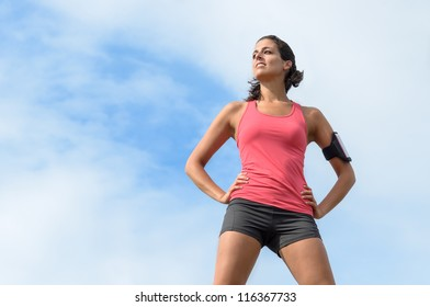 Confident sportswoman standing. Successful fitness woman on sky background.