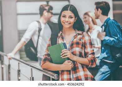 Confident student. Happy young woman holding books and looking at camera while her friends standing in the background