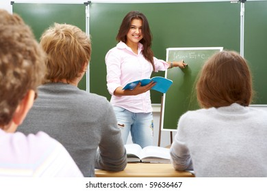 Confident student pointing at formula on blackboard and looking at camera with smile