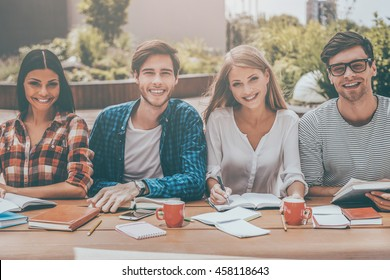 Confident students. Group of happy young people working together and looking at camera while sitting at the wooden desk outdoors