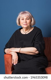 Confident stylish european mature aged woman sitting at chair, she wearning at black dress. Portrait of a stylish older senior business woman, 60s gray-haired lady. Deep blue background.