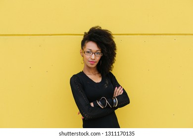 Confident stylish professional woman against yellow wall.