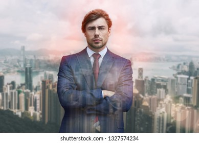 Confident and succesful. Close-up portrait of attractive man in suit keeping his arms crossed while standing against of cityscape background.