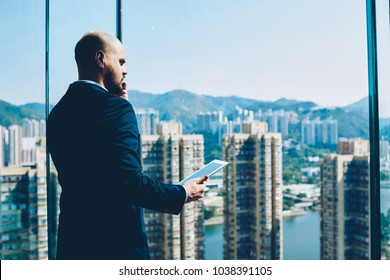 Confident successful banker in suit solving business problems on smartphone while looking out of window with amazing metropolis outdoors.Serious proud ceo with tablet in hands calling on cellular