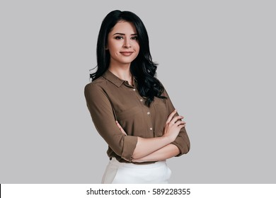 Confident and successful. Beautiful young woman in smart casual wear keeping arms crossed and looking at camera with smile while standing against grey background
